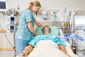 critical care ICU nurse adjusting patient's pillow in hospital room noddle Voxello